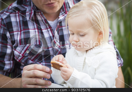 Adorable Little Girl Eating a Cookie with Daddy stock photo, Adorable Little Girl Eating a Cookie with Daddy Outside. by Andy Dean