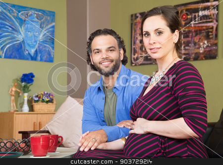 Happy Expecting Couple stock photo, Happy mixed expecting couple holding hands in room by Scott Griessel