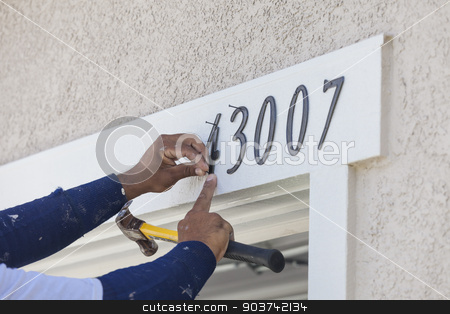 House Painter Contractor Nails Address Numbers to House Facade stock photo, House Painter Contractor Nails Address Numbers onto House Facade. by Andy Dean