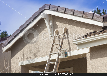 Ladder Leaning Up Against A House Ready For New Paint stock photo, Construction Ladder Leaning Up Against A House Ready For New Paint. by Andy Dean