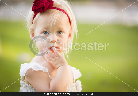 Adorable Little Girl Wearing White Dress In A Grass Field stock photo, Beautiful Adorable Little Girl With Her Hand On Her Face Wearing White Dress In A Grass Field. by Andy Dean