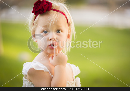 Adorable Little Girl Wearing White Dress In A Grass Field stock photo, Beautiful Adorable Little Girl With Her Finger on Her Mouth Wearing White Dress In A Grass Field. by Andy Dean