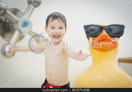 Mixed Race Boy Having Fun at the Water Park stock photo, Mixed Race Boy Having Fun at the Water Park with Large Rubber Duck in the Background. by Andy Dean