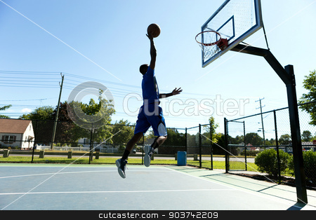 Basketball Dunk Outdoors stock photo, Young basketball player driving to the hoop for a high flying slam dunk. by Todd Arena