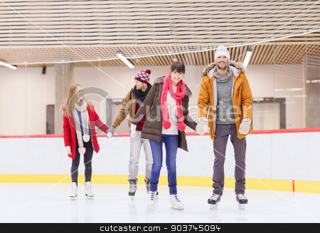 happy friends on skating rink stock photo, people, friendship, sport and leisure concept - happy friends on skating rink by Syda Productions
