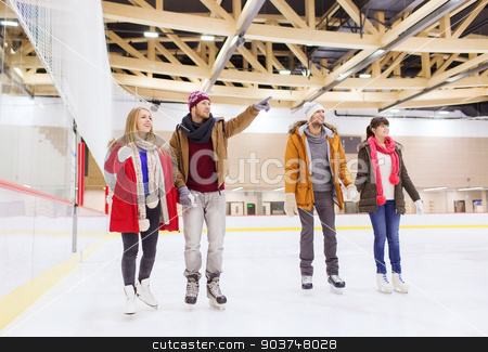 happy friends pointing finger on skating rink stock photo, people, friendship, sport, gesture and leisure concept - happy friends pointing finger on skating rink by Syda Productions