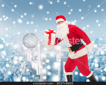 man in costume of santa claus with gift box stock photo, christmas, holidays and people concept - man in costume of santa claus running with gift box over snowy city background by Syda Productions