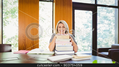 Smiling blonde mature student with stack of books stock photo, Smiling blonde mature student with stack of books in library by Wavebreak Media