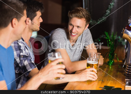 Happy friends catching up over pints stock photo, Happy friends catching up over pints in a bar by Wavebreak Media