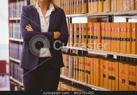 Mature female librarian posing with crossed arms stock photo, Mature female librarian posing with crossed arms in library by Wavebreak Media