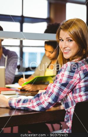 Portrait of a smiling student sitting at desk looking at camera stock photo, Portrait of a smiling student sitting at desk looking at camera in library by Wavebreak Media