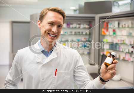 Handsome pharmacist holding medicine jar stock photo, Handsome pharmacist holding medicine jar at the hospital pharmacy by Wavebreak Media