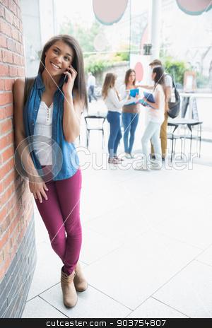 Pretty student talking on her phone stock photo, Pretty student talking on her phone at the university by Wavebreak Media