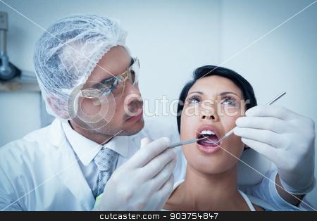 Male dentist examining womans teeth stock photo, Male dentist examining womans teeth in the dentists chair by Wavebreak Media