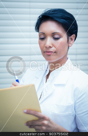 Female dentist reading reports stock photo, Serious female dentist reading reports by Wavebreak Media