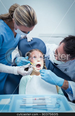 Dentist with assistant examining girls teeth stock photo, Dentist with assistant examining girls teeth in the dentists chair by Wavebreak Media