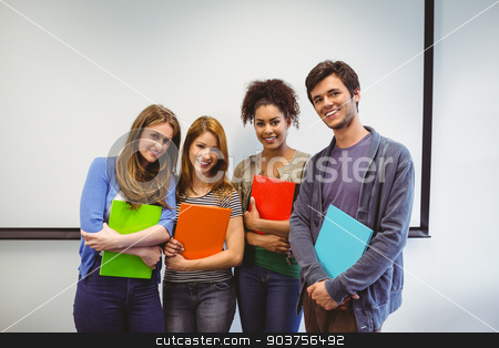 Students standing and smiling at camera holding notepads stock photo, Students standing and smiling at camera holding notepads in classroom by Wavebreak Media