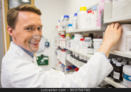 Handsome pharmacist taking medicine from shelf stock photo, Handsome pharmacist taking medicine from shelf at the hospital pharmacy by Wavebreak Media