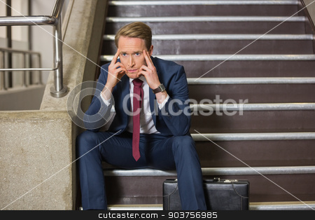 Stressed businessman sitting on steps stock photo, Stressed businessman sitting on steps in office building by Wavebreak Media