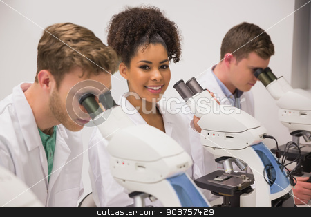 Medical students working with microscope stock photo, Medical students working with microscope at the university by Wavebreak Media