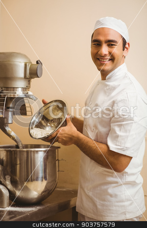 Baker pouring flour into large mixer stock photo, Baker pouring flour into large mixer in a commercial kitchen by Wavebreak Media