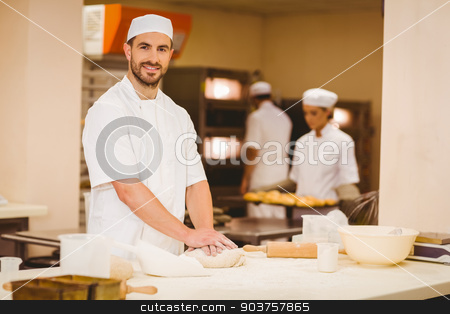 Baker kneading dough at a counter stock photo, Baker kneading dough at a counter in a commercial kitchen by Wavebreak Media