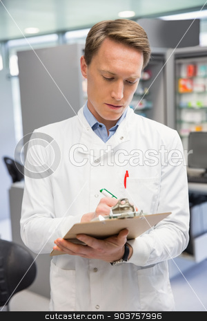 Handsome pharmacist writing on clipboard stock photo, Handsome pharmacist writing on clipboard at the hospital pharmacy by Wavebreak Media