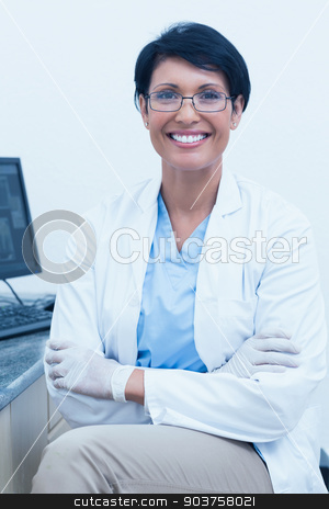 Smiling female dentist with arms crossed stock photo, Portrait of smiling female dentist with arms crossed by Wavebreak Media