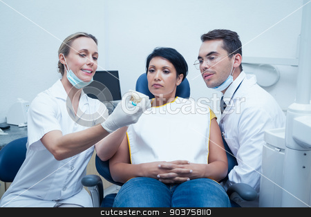 Dentists showing woman prosthesis teeth stock photo, Female dentist with assistant showing woman prosthesis teeth by Wavebreak Media