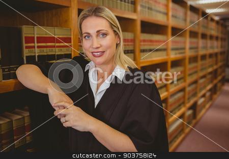Smiling lawyer leaning on shelf stock photo, Smiling lawyer leaning on shelf in library by Wavebreak Media