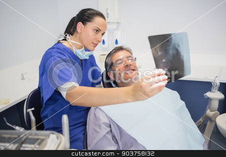 Smiling dentist showing x-ray to her patient  stock photo, Smiling dentist showing x-ray to her patient in dental clinic by Wavebreak Media