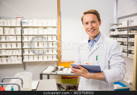 Happy pharmacist using tablet pc stock photo, Happy pharmacist using tablet pc at the hospital pharmacy by Wavebreak Media
