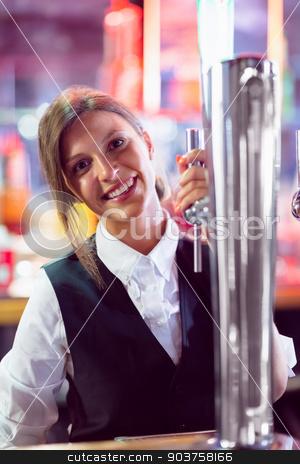 Pretty barmaid pulling pint of beer stock photo, Pretty barmaid pulling pint of beer in a bar by Wavebreak Media