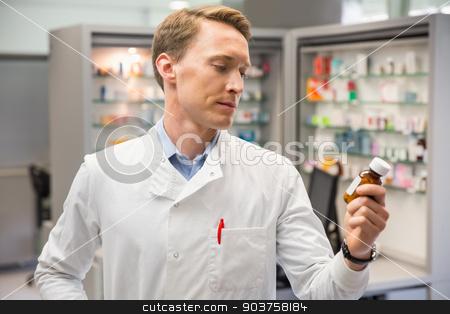 Handsome pharmacist looking at medicine stock photo, Handsome pharmacist looking at medicine at the hospital pharmacy by Wavebreak Media