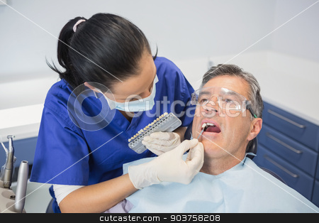 Dentist comparing teeth whitening stock photo, Dentist comparing teeth whitening of her patient in dental clinic by Wavebreak Media
