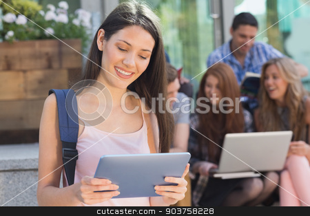 Pretty student using her tablet pc on campus stock photo, Pretty student using her tablet pc on campus at the university by Wavebreak Media