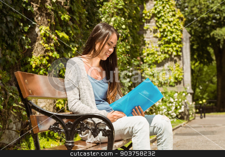 Smiling student sitting on bench and reading book stock photo, Smiling student sitting on bench and reading book in park at school by Wavebreak Media