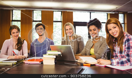 Smiling students working together on an assignment stock photo, Smiling students working together on an assignment by Wavebreak Media