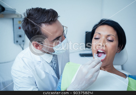 Male dentist examining womans teeth stock photo, Male dentist examining womans teeth in the dentists chair by Wavebreak Media