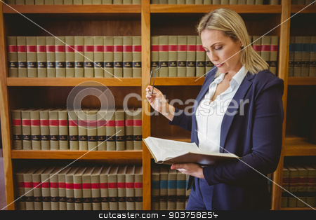 Focused librarian reading book and holding reading glasses stock photo, Focused librarian reading book and holding reading glasses in library by Wavebreak Media