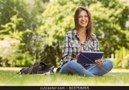 Smiling student sitting and using tablet pc stock photo, Smiling student sitting and using tablet pc in park at school by Wavebreak Media