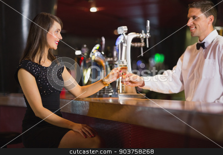 Handsome barman serving champagne to customer stock photo, Handsome barman serving champagne to customer in a bar by Wavebreak Media