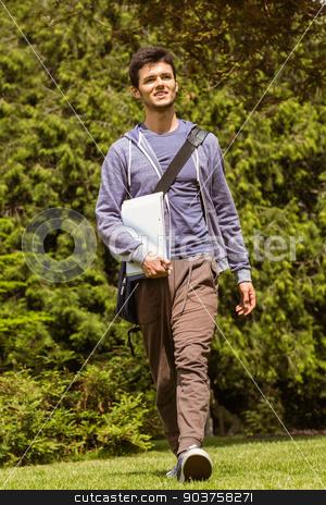 Student walking with shoulder bag and holding notepad stock photo, Student walking with shoulder bag and holding notepad in park at school by Wavebreak Media