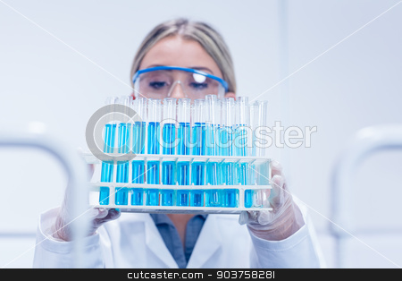 Science student holding tray of test tubes stock photo, Science student holding tray of test tubes at the university by Wavebreak Media