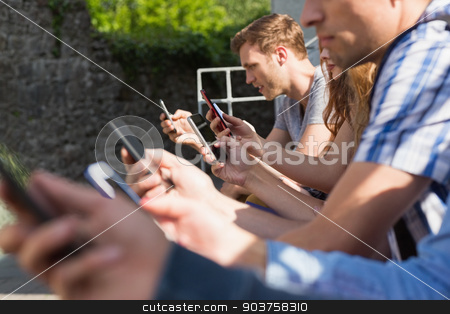 Happy students sitting in a row texting stock photo, Happy students sitting in a row texting at the university by Wavebreak Media