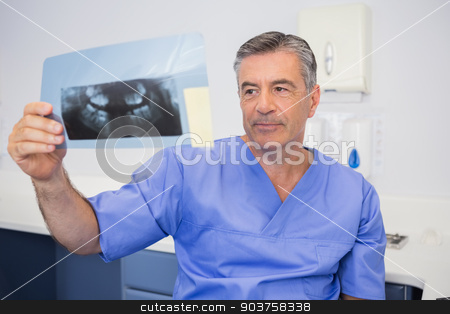 Thoughtful dentist studying x-ray attentively stock photo, Thoughtful dentist studying x-ray attentively in dental clinic by Wavebreak Media