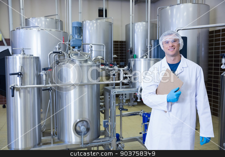 Man holding a clipboard standing in front of the container stock photo, Man holding a clipboard standing in front of the container in the factory by Wavebreak Media