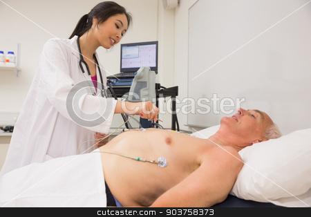 Medical student practicing on older man stock photo, Medical student practicing on older man at the university by Wavebreak Media