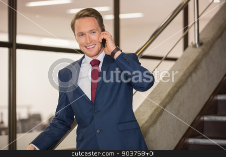Handsome businessman on the phone stock photo, Handsome businessman on the phone in office building by Wavebreak Media