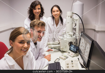 Biochemistry students using large microscope and computer stock photo, Biochemistry students using large microscope and computer at the university by Wavebreak Media